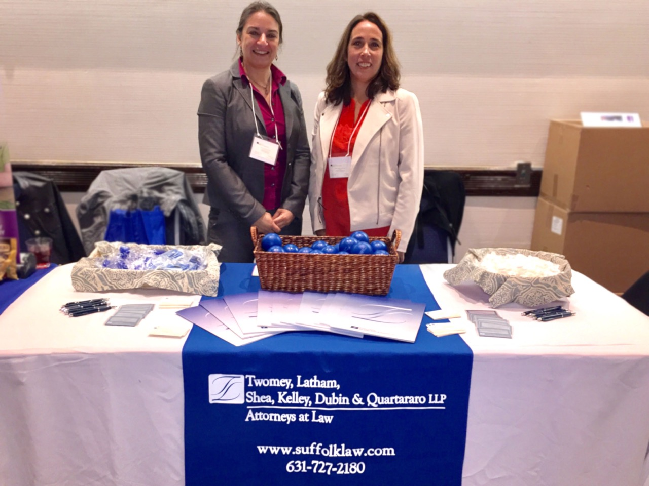 partner attorneys Anne Marie Goodale and Laura Dunathan in front of Twomey Latham booth table